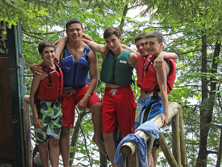 Group of boys in trees near lake in life jackets