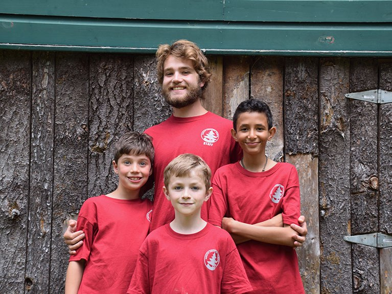 Counselor and three boys smiling