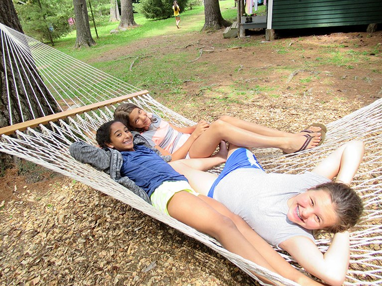 Three girls smiling in hammock