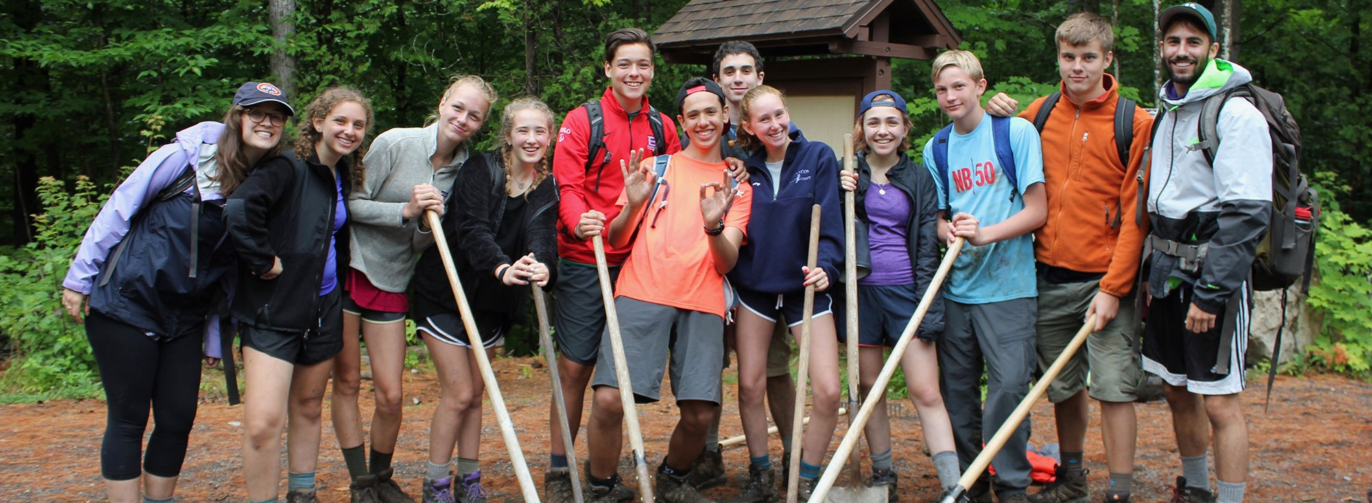 Campers Smiling and Holding Shovels