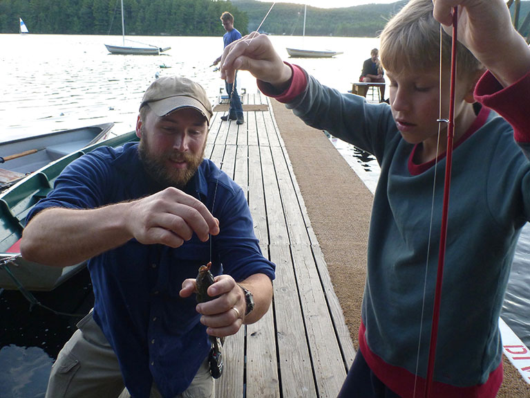 counselor showing camper how to take hook out of caught fish's mouth