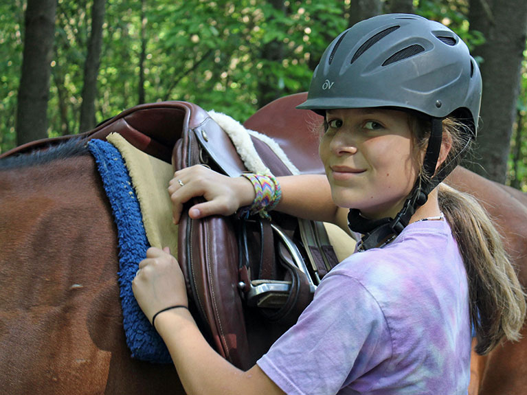 camper putting saddle on horse