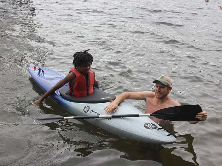 counselor helping camper in kayak