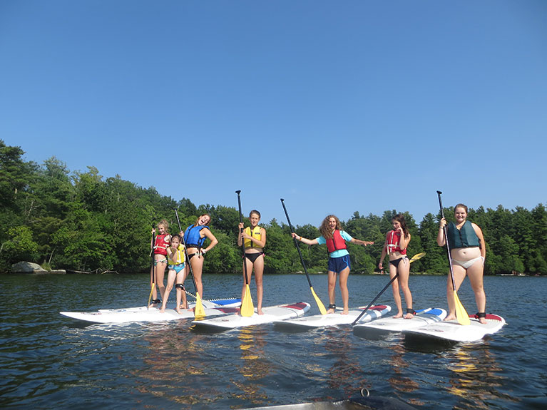 group of campers on paddle boards in lake