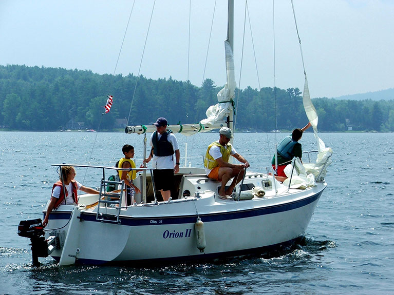 campers and instructor on larger sailboat in lake