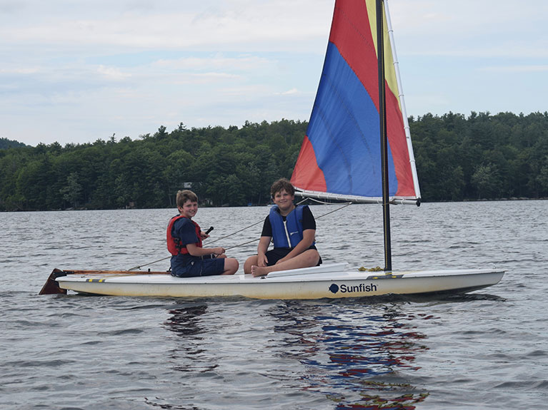 two boys in lake on sail boat
