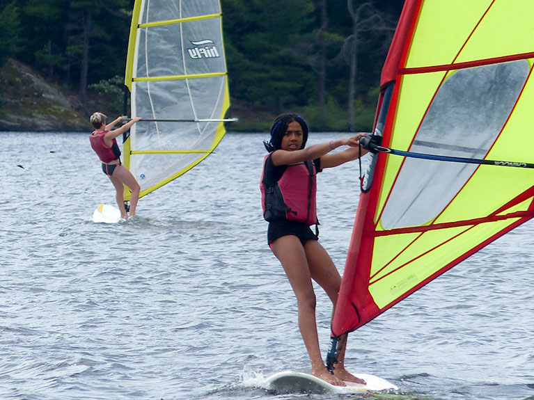 campers windsurfing on lake