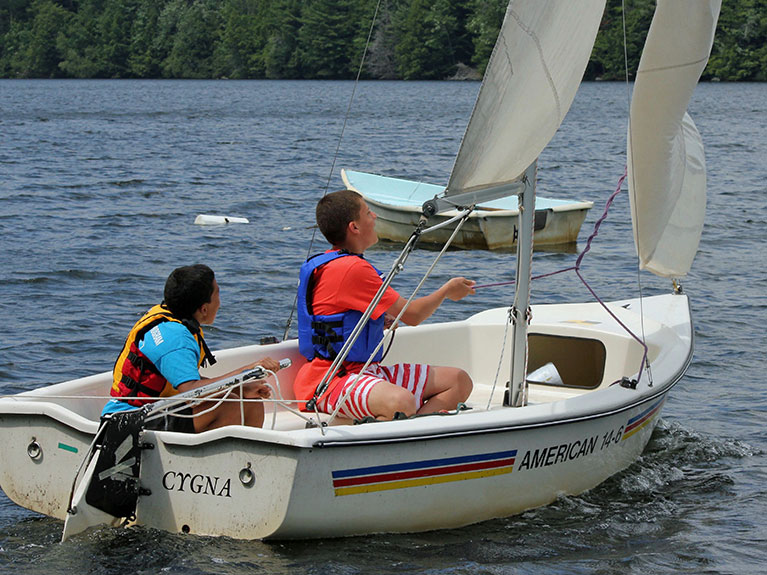 Campers sailing on lake in boat