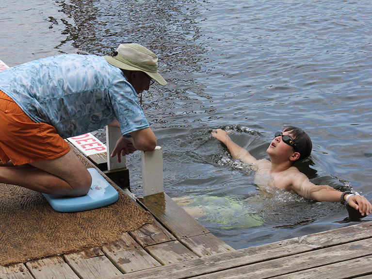 Instructor on dock teaching camper to swim